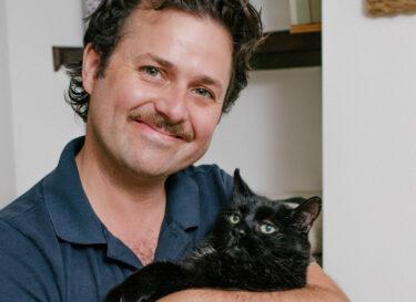 oprichter van bedrijf voor kattenvoer met zijn dikke, zwarte kat