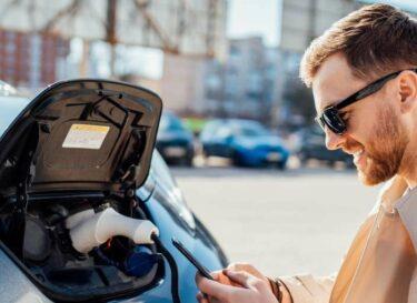 Man casual smartphone elektrische auto opladen change inc adobe stock