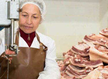 Vrouw snijdt vlees in een fabriek adobe stock change inc